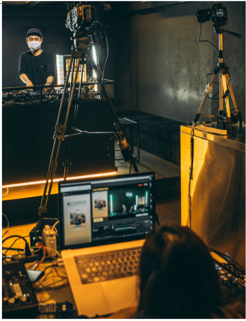 A live streaming studio set up with tripods, cameras, host and editor. Photo by Heshan Perera on Unsplash